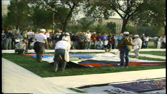Group of People Unwrapping AIDS Quilt on Great Lawn