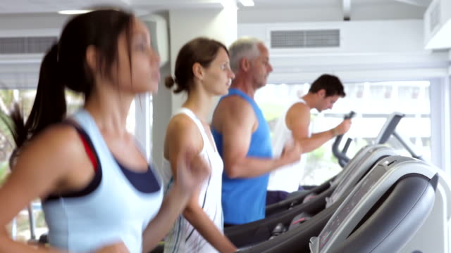 group of people using running machines - cross trainer stock videos and b-roll footage
