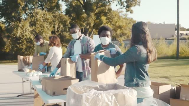 group of people volunteer at food drive during coronavirus pandemic - charity benefit stock videos & royalty-free footage