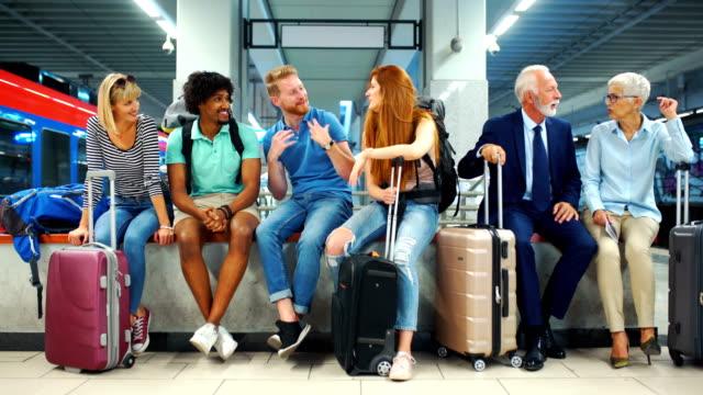 vídeos de stock, filmes e b-roll de grupo de pessoas esperando por um trem. - sentando
