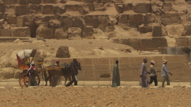 a group of people walk with a horse and cart past one of giza's pyramids, egypt. - cart stock videos & royalty-free footage