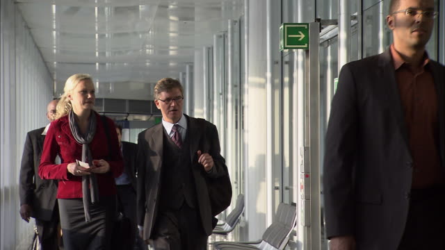MS Group of people walking down airport corridor after landing/ Munich, Germany