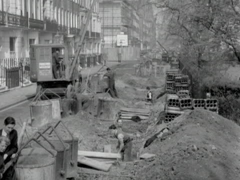 group of people watch workmen dig up a road. 1955. - number of people stock videos & royalty-free footage