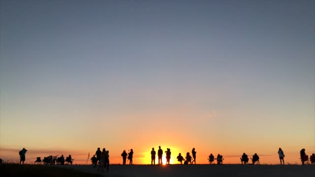 vídeos de stock e filmes b-roll de group of people watching sunset - retroiluminado