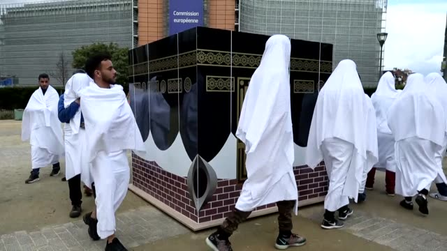 a group of people wearing white clothing symbolizing 'ihram' circle a makeshift kaaba during a demonstration organized by alharamain watch to protest... - hajj stock videos & royalty-free footage
