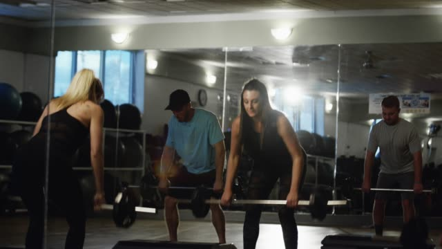 a group of people weight lift in an exercise class - cross training stock videos & royalty-free footage