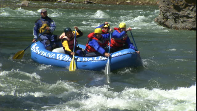 A group of people whitewater raft down a river.