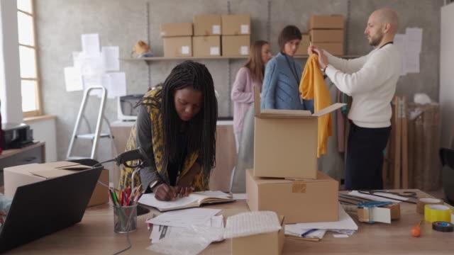 gruppo di persone che lavorano presso l'ufficio del negozio online, prendono ordini e impacchettano vestiti - vendere video stock e b–roll