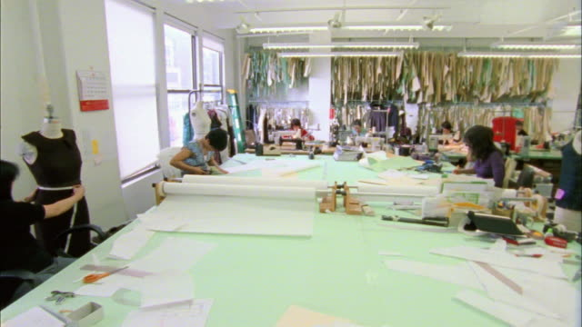 ws pan group of people working in busy fashion designer's workshop / new york city, new york, usa  - halle gebäude stock-videos und b-roll-filmmaterial