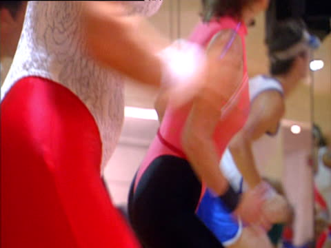 vídeos de stock e filmes b-roll de group of people working out in aerobics class with woman wearing eighties style red leggings and white leotard and man in blue shorts and string vest - body de ginástica