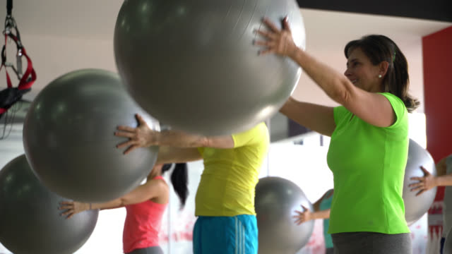 group of people working out their arms with exercise balls at the gym following instructor - affascinante video stock e b–roll