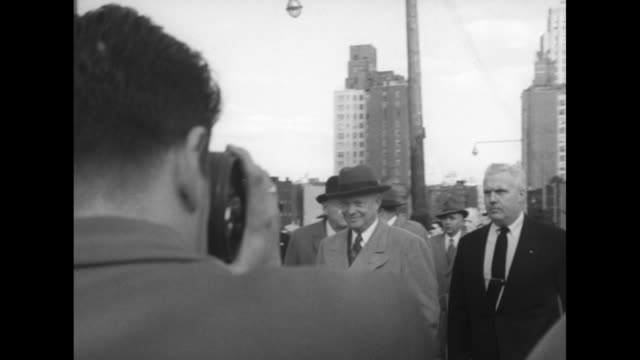 vidéos et rushes de group of photographers, cameras with flash attachments / us president-elect dwight eisenhower with john foster dulles walking down sidewalk, others... - photographe