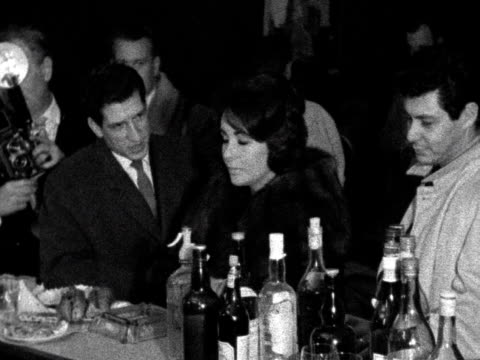 A group of photographers surround Elizabeth Taylor and Eddie Fisher at a bar in London Airport Taylor smiles demurely at the camera 1960
