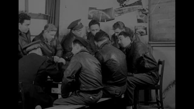 group of pilots and flight crew gathered around picnic table in briefing room as officer listens to them during mission debriefing; officer asks... - 空爆点の映像素材/bロール