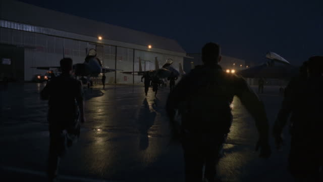 a group of pilots running toward their aircrafts. - 機械工点の映像素材/bロール