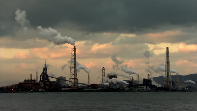 A group of plants in evening view Dolly shot aboard from Dokai Bay Billowing smokes flowing from right to left Clouds in madder color in the back A...