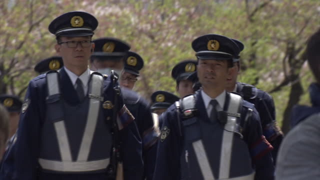 group of police officers on patrol in hiroshima peace memorial park during 2016 g7 hiroshima foreign minister's meeting period. - armi di distruzione di massa video stock e b–roll
