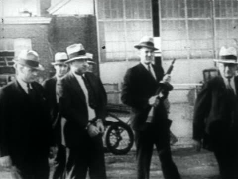 vidéos et rushes de pan group of police one with gun escorting machine gun kelly outdoors / memphis - 1933