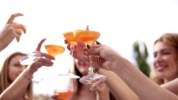 Group of pretty girls are celebrating and drinking cocktails from big glasses. Cheers. Outdoors. Aim frame of glasses, blurred background. Slow motion
