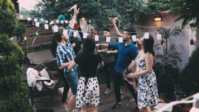 vidéos et rushes de groupe de jolies jeunes gens ont une fête d'été dans une cour arrière - partage