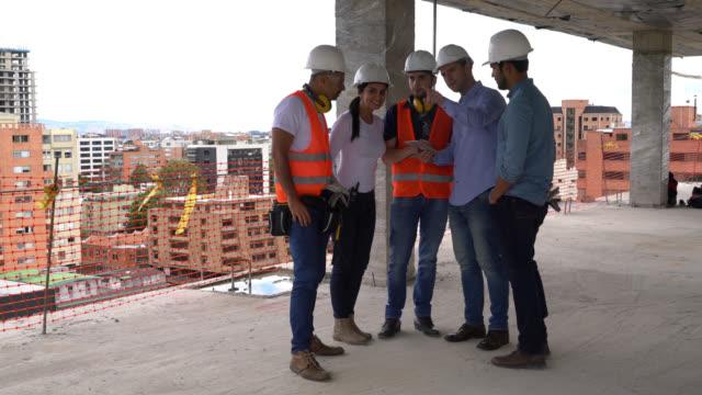 Groupe d'architectes, des ingénieurs et des ouvriers en regardant quelque chose pointe vers le chef, puis une tablette numérique