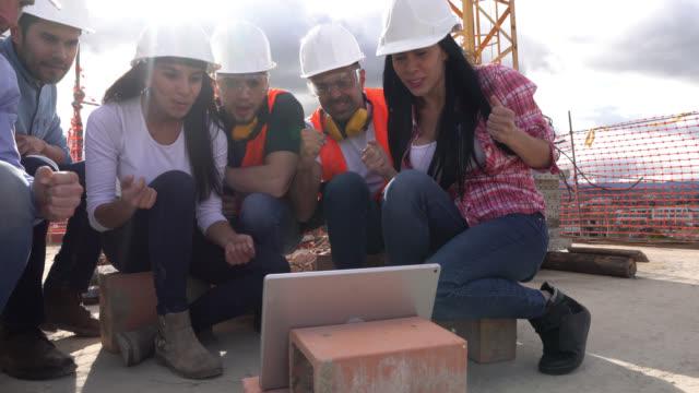 gruppe von fachleuten auf einer baustelle eine pause gerade ein fußballspiel auf einem digitalen tablet - verzückt stock-videos und b-roll-filmmaterial