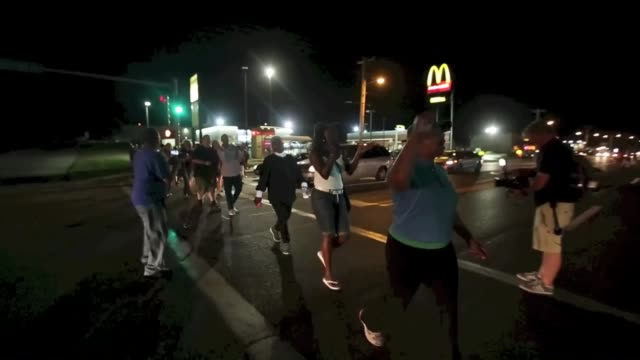 a group of protester gather along west florissant avenue and block the street marking the oneyear anniversary of the shooting of michael brown in... - 2014 bildbanksvideor och videomaterial från bakom kulisserna