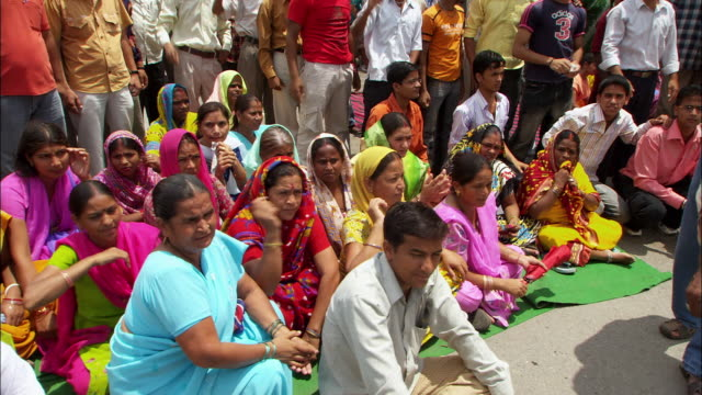 a group of protesters gesture, chant and wave as they sit in a city street in the uttarkashi district of india. available in hd. - demonstration stock videos and b-roll footage