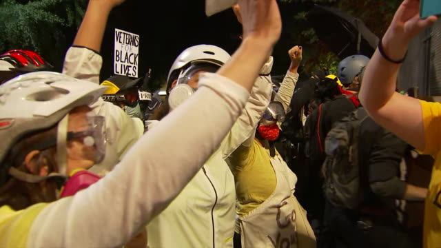 group of protesters raise up their hands during a protest outside the federal courthouse in portland, oregon. - hand raised stock videos & royalty-free footage