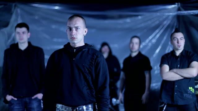 vídeos de stock, filmes e b-roll de grupo de punks de pé no armazém - concorrente