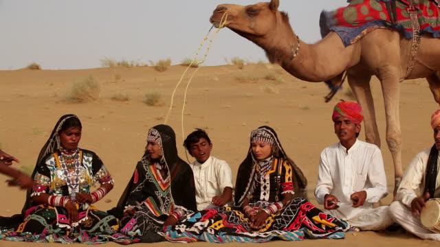 group of rajasthani people playing traditional musical instrument on desert, sam desert, jaisalmer, rajasthan, india - arbetsdjur bildbanksvideor och videomaterial från bakom kulisserna