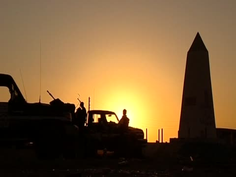 Group of rebels by jeep in silhouette at sunset