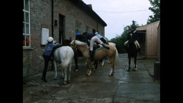 group of riders mount horses in stableyard; 1986 - recreational horse riding stock videos & royalty-free footage