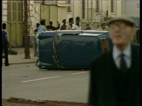 vídeos de stock e filmes b-roll de group of rioters set fire to overturned car brixton riots; apr 81 - 1981