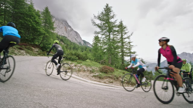 group of road cyclists speeding up the mountain road on a cloudy day - females stock videos & royalty-free footage