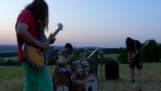 group of rock musicians play instruments in meadow at sunset
