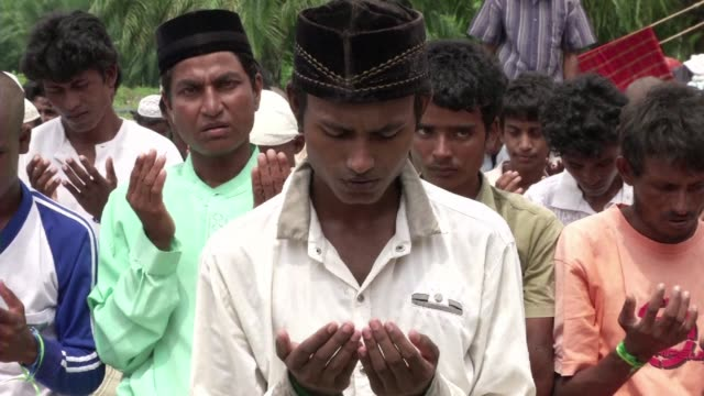 A group of Rohingya migrants offer Friday prayer at a makeshift refugee camp set up in Langsa Indonesia