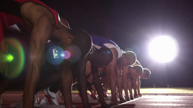 vídeos y material grabado en eventos de stock de a group of runners crouch in their starting positions before beginning to race. - atleta atletismo