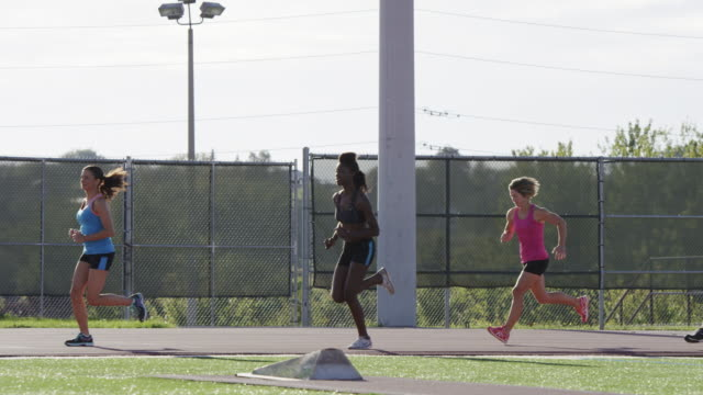 Group of runners running a race on a track in the city