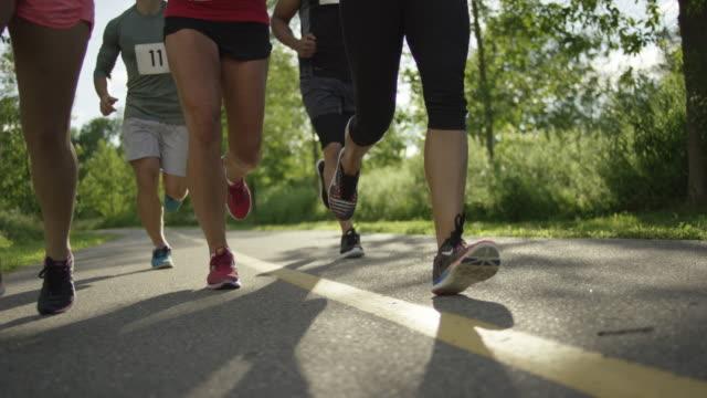 vídeos de stock e filmes b-roll de grupo de corredores correr fora - desportista