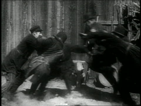 b/w 1914 group of running keystone kops stopping + fallling down / feature - 1914 stock videos & royalty-free footage