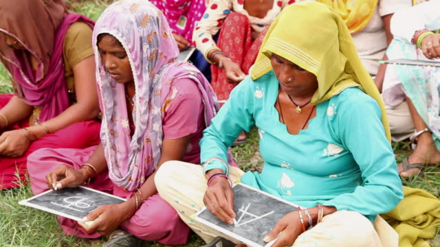 group of rural women writing on a slate, haryana, india - bremskeil stock-videos und b-roll-filmmaterial