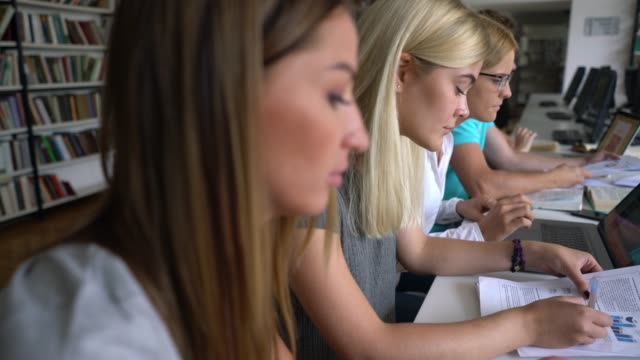 図書、文書、ノートパソコンを使って勉強する図書館のロシアの学生のグループ - 公共図書館点の映像素材/bロール