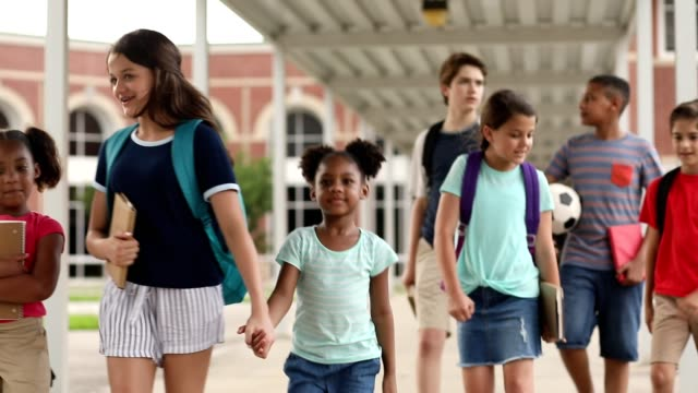 group of school children, friends walking together on campus. - mixed age range stock videos & royalty-free footage
