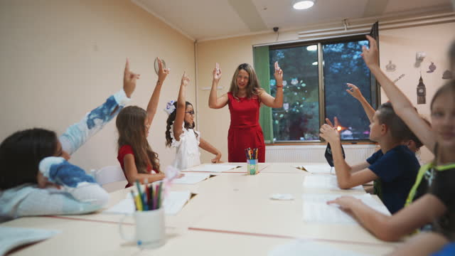 group of school children raising their hands to ask or answer questions - elementary school building stock videos & royalty-free footage