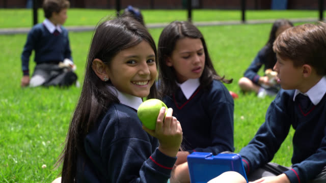 group of school friends talking while enjoying their snacks during break and little girl turning to face camera holding an apple and smiling - school uniform stock videos & royalty-free footage