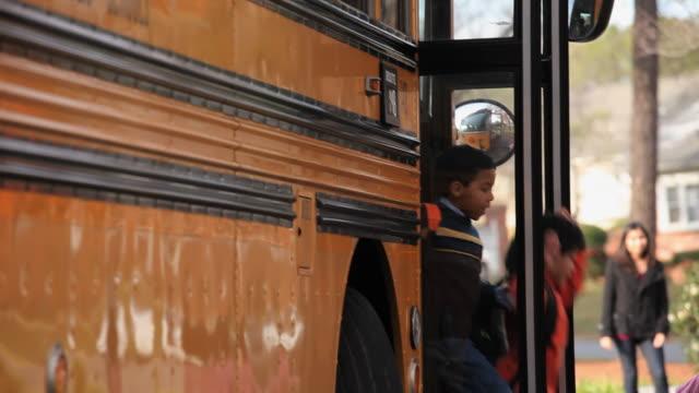 ms td group of school students (4-7) disembarking school bus and running towards parents waiting on sidewalk / richmond, virginia, usa - 降り立つ点の映像素材/bロール