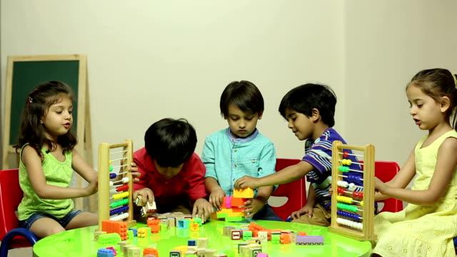 Group of school students making building blocks