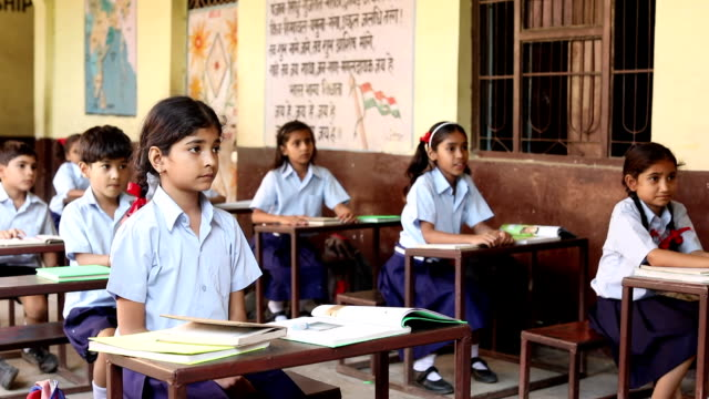group of school students raising hands in classroom, haryana, india - india video stock e b–roll