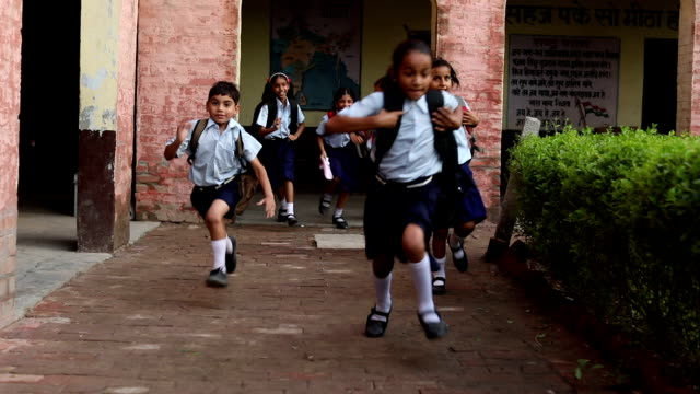 group of school students running in school, haryana, india - india video stock e b–roll